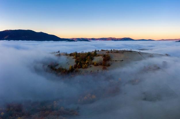 Zonsopgang boven berghellingen bedekt met grijze mist