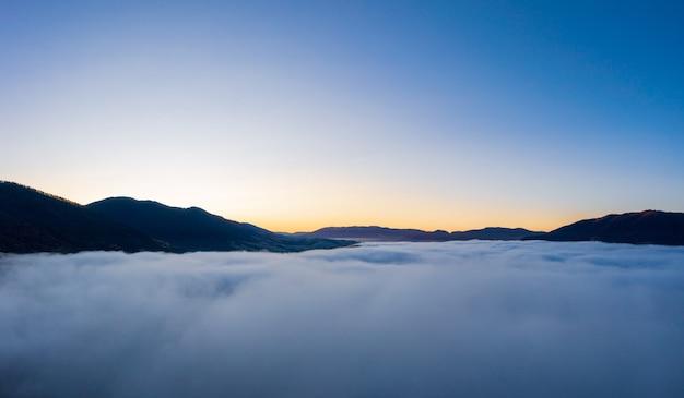 Zonsopgang boven bergheuvels bedekt met grijze mist