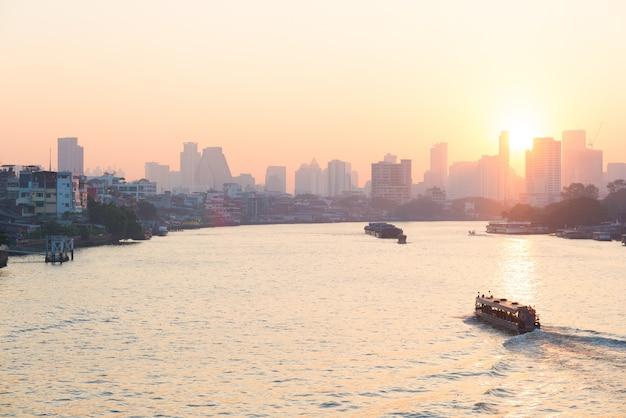 Zonsopgang boven de schilderachtige skyline in bangkok, thailand, bekeken in tegenlicht bij zonsopgang met oranjerode heldere hemel.