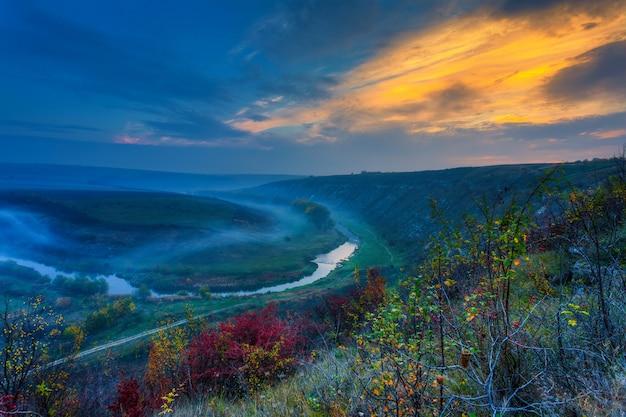 Zonsopgang boven een mistige kleine rivier
