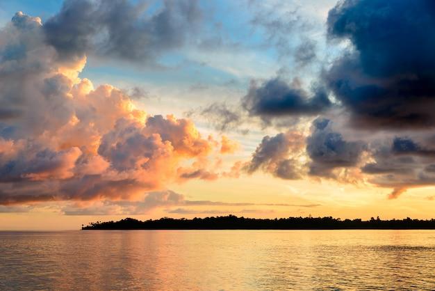 Zonsopgang dramatische hemel op overzees, tropisch woestijnstrand, geen mensen, stormachtige wolken