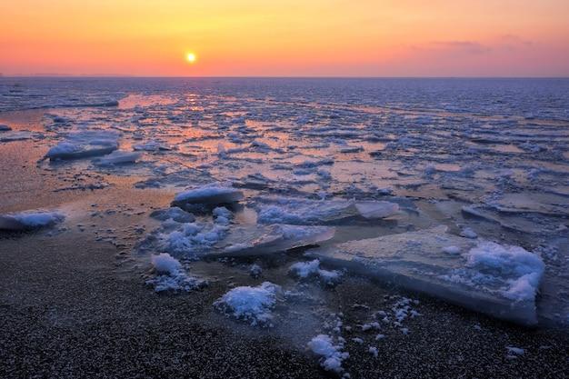 Zonsopgang en bevroren zee. prachtig winterlandschap met meer in de ochtendtijd.
