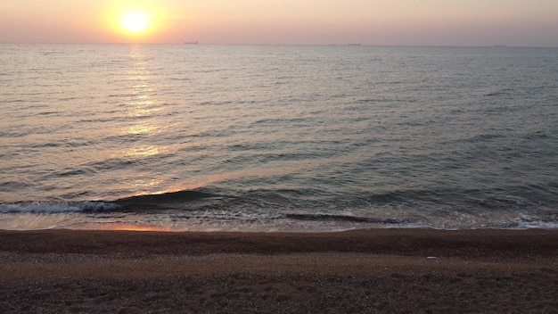 Zonsopgang en golven op de zee, uitzicht vanaf het zandstrand.