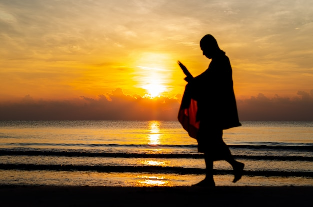 Zonsopgang met bezinning over het overzees en het strand die vage silhouetfoto van boeddhistische monnik hebben.