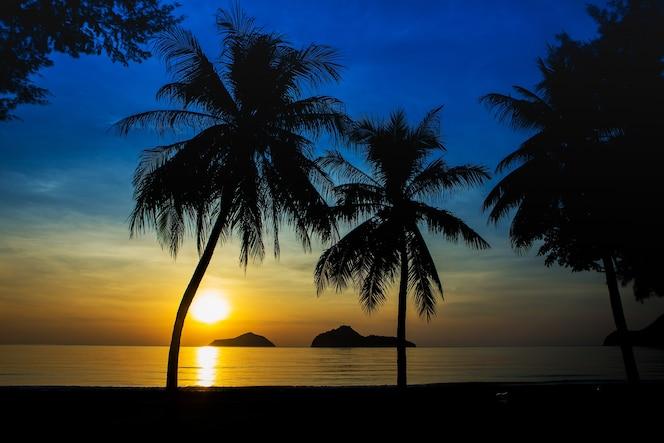Zonsopgang op zee met eilanden en kokospalmen.