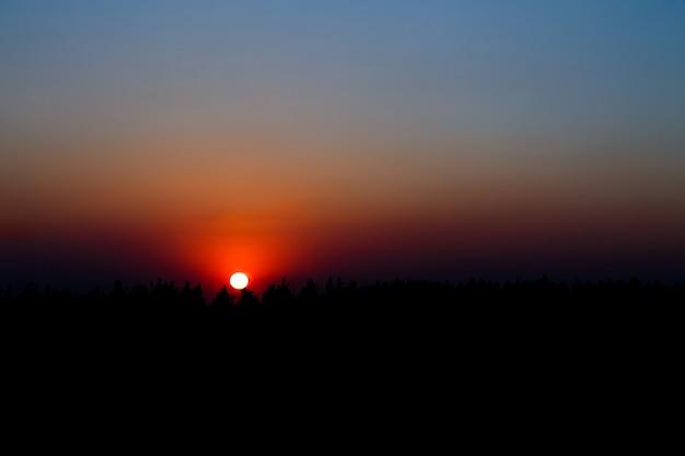 Zonsopgang/zonsondergang met gloeiende kleurrijke luchten. verbazingwekkend natuurlijk zonlicht, dat de aarde verlicht. magische kleuren die vanaf de horizon stralen en stralen. dag eindigt ergens en begint ergens anders