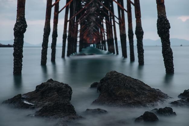 Zonsopgangdawn met rotsen en brug in lange blootstelling