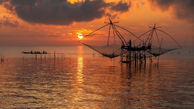 Zonsopganghemel met visser op vierkante netto onderdompeling en toerismeboot bij pakpra-dorp, phatthalung-provincie, thailand