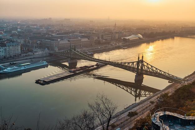 Zonsopgangmening in de rivier van boedapest, van donau en liberty-brug die door de ochtendzon wordt verlicht