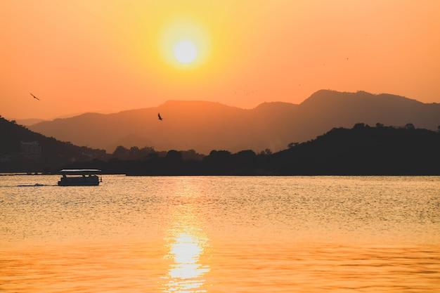 Zonstijging in de ochtend bij op meer pichola in udaipur, india, uitstekende stijl