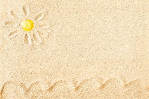 Zonverf op zand met gele zeeschelp, bovenaanzicht