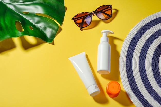 Zonwering objecten. vrouw hoed met zonnebril en beschermingscrème spf flat lag op gele achtergrond. strandaccessoires. zomer reizen vakantie concept