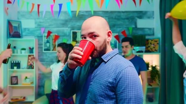 Zoom in op een jonge man die alcohol drinkt terwijl hij aan het feesten is met zijn vrienden op een universiteitsfeest met neonlichten