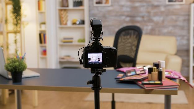 Zoom in op een lege influencer-kamer met cosmetica op tafel en professionele opnameapparatuur.
