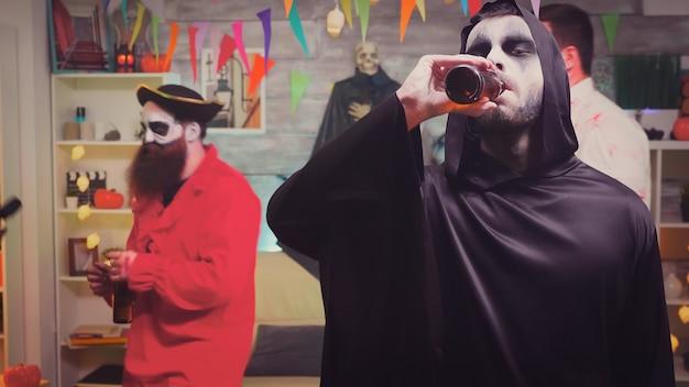 Zoom in op een man verkleed als magere hein die bier drinkt op halloween-feest.