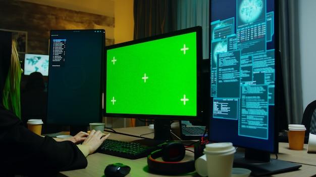Zoom in schot van hacker meisje voor computer met groen scherm. cybercrimineel met hoodie.