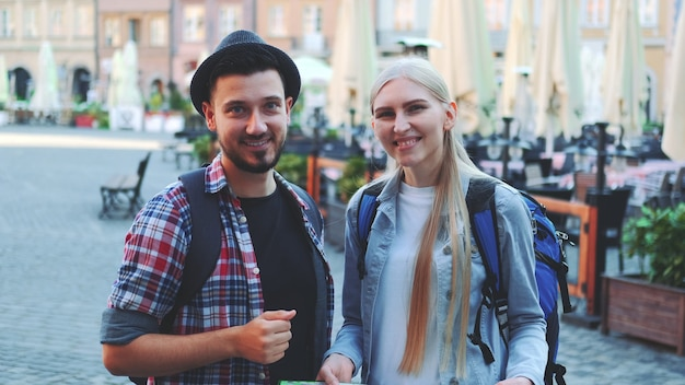Zoom shot van toeristen die kaart houden en naar de camera glimlachen. ze staan op een groot marktplein van een oude europese stad.