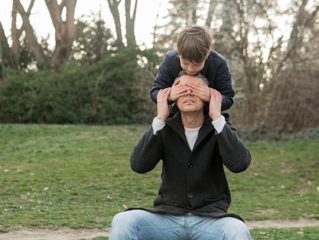 Zoon bedekt de ogen van zijn vader