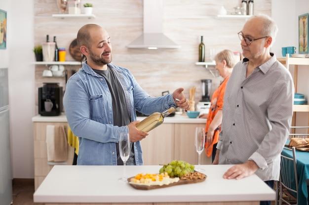 Zoon die een wijnfles in de keuken vasthoudt terwijl hij een gesprek voert met zijn oudste. wfe en moeder bereiden heerlijke lunch voor familiebijeenkomst.