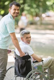 Zoon die met gehandicapte vader in rolstoel bij park loopt