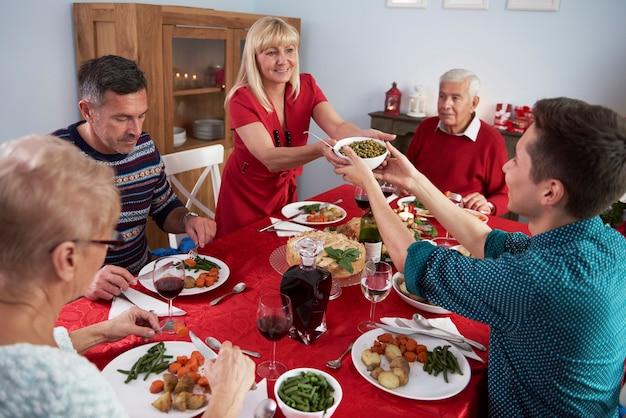 Zoon die moeder helpt bij het kerstdiner