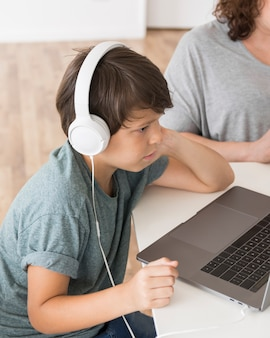 Zoon die op laptop naast mamma kijkt