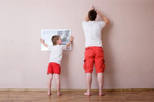 Zoon die vader helpt om beeld op de muur te hangen, vaderschapsconcept, gelukkige kinderjaren