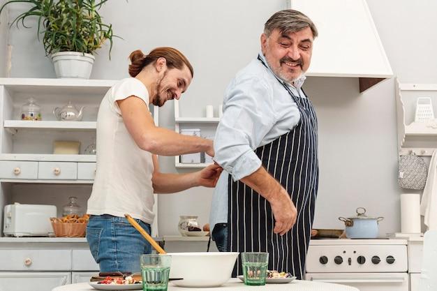 Zoon die vader met keukenschort helpt
