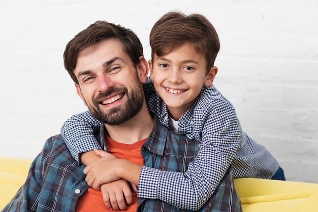 Zoon die zijn glimlachende vader omhelst