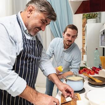 Zoon die zijn vader het koken bekijkt