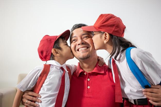 Zoon en dochter kussen vader op de wang
