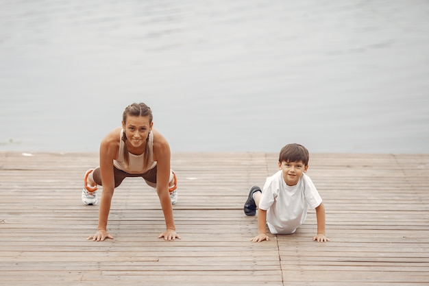 Zoon en moeder doen oefeningen in het zomerpark. familie aan het water.