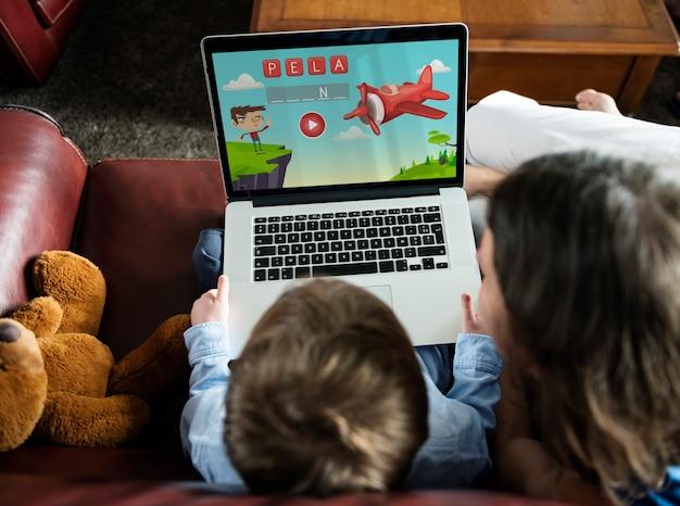 Zoon en moeder met behulp van laptop e-learning game onderwijs thuis