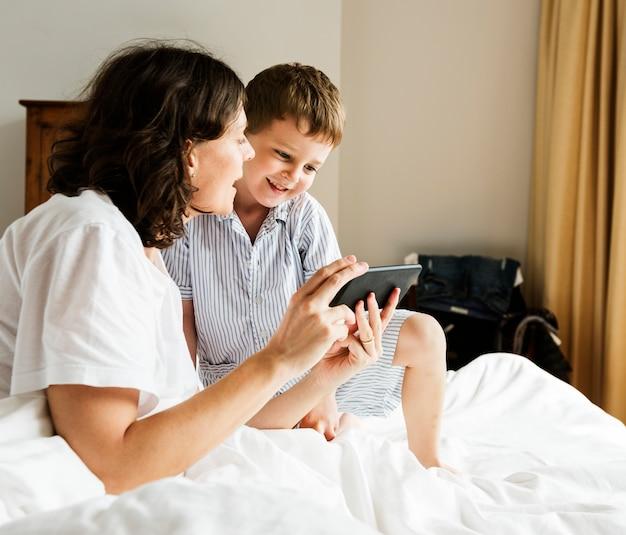 Zoon en moeder met behulp van slimme telefoon in pyjama