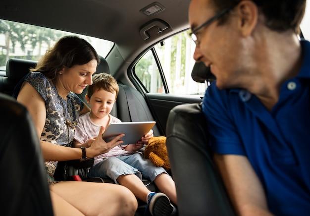 Zoon en moeder met behulp van tablet op de auto