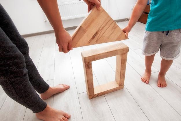 Zoon en moeder spelen in de kamer en bouwen huis uit houten blokken