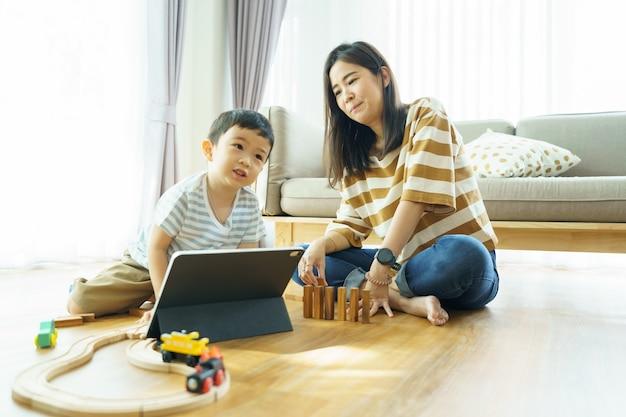 Zoon en moeder spelen samen speelgoed. leerontwikkeling verbeteren. toon liefde in het gezin