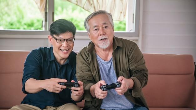Zoon en oude vader spelen videogame met joystickcontrollers in de woonkamer in huis
