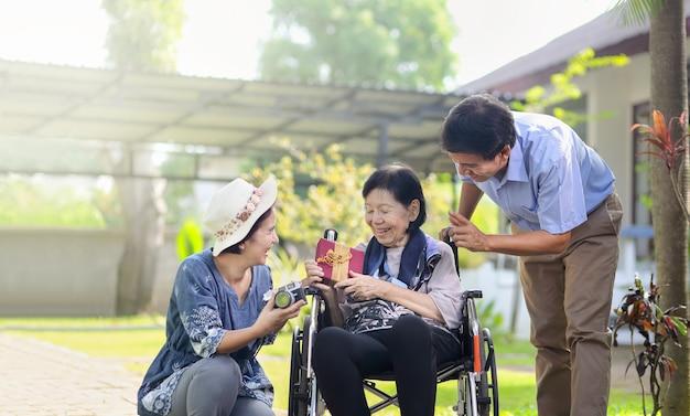 Zoon en schoondochter cadeau bejaarde moeder in achtertuin