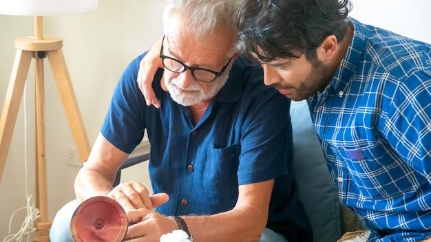 Zoon en senior vader kijken naar global kaart en gebaren op zijn samen in de woonkamer