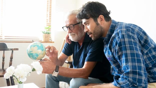 Zoon en senior vader kijken naar global kaart en gebaren op zijn samen