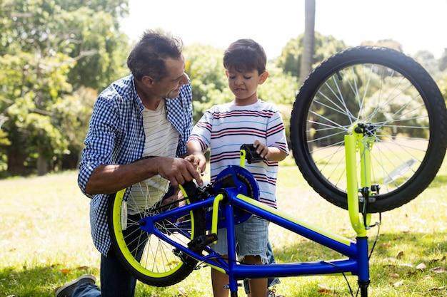Zoon en vader die hun fiets in park herstellen