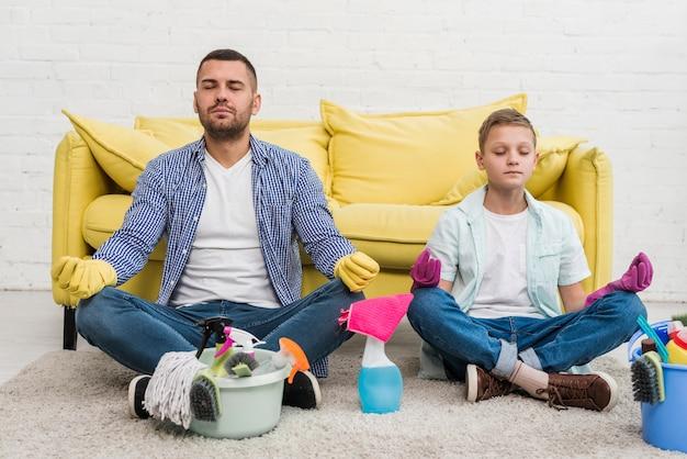 Zoon en vader doen yoga na het schoonmaken