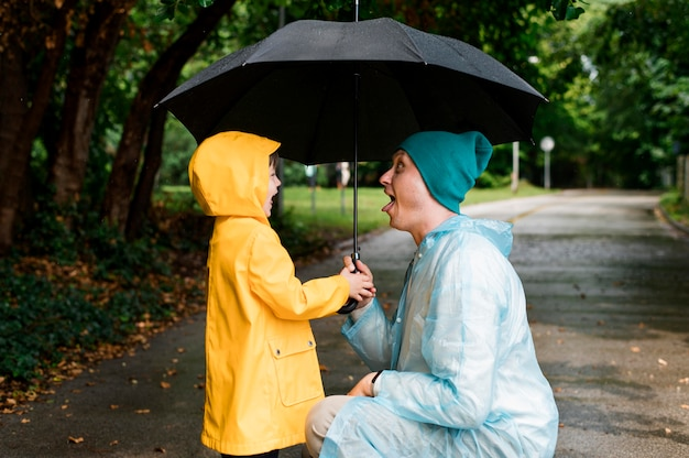 Zoon en vader kijken elkaar onder een paraplu