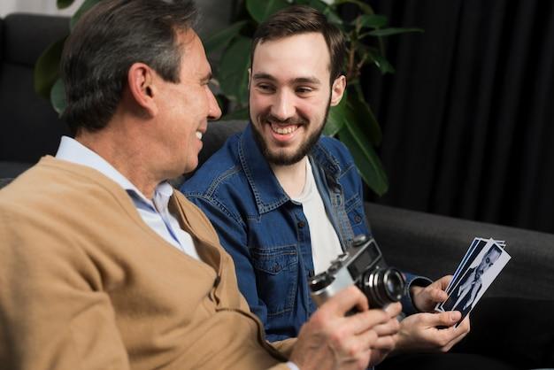 Zoon en vader kijken naar foto's in de woonkamer