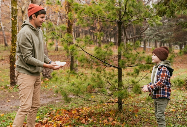 Zoon en vader spelen samen buiten in de natuur