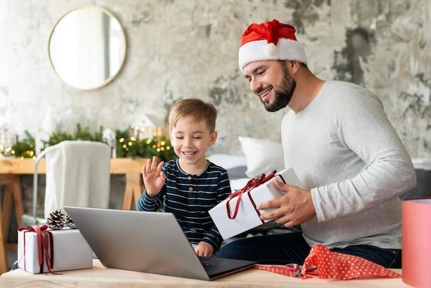 Zoon en vader zwaaien naar familieleden op videogesprek op eerste kerstdag