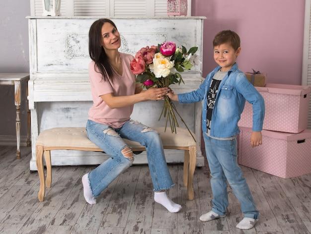Zoon geeft moeder een boeket bloemen, moederdag concept