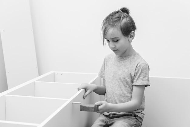 Zoon helpt zijn vader om thuis nieuwe meubels in elkaar te zetten. zelf meubelmontage. jeugd, levensstijl concept. schattige jongen assembleert zelf een boekenplank.