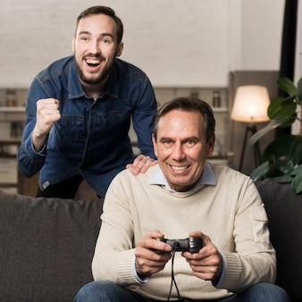 Zoon juichende vader die videogames speelt